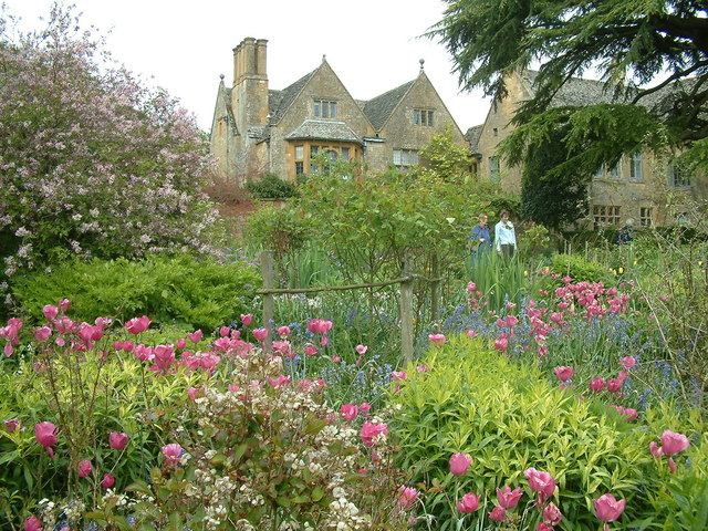 Cotswold gardens with house and couple walking through wildflower garden