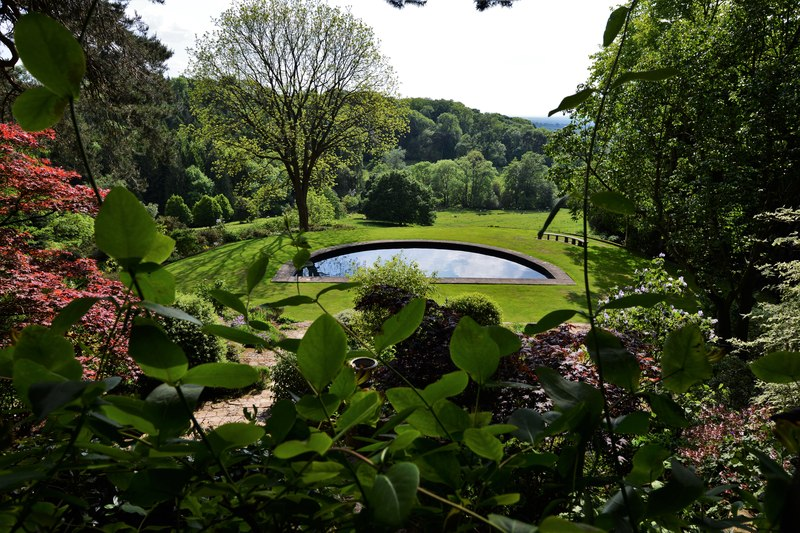 Cotswold gardens looking through leafy foliage to a half-moon pond