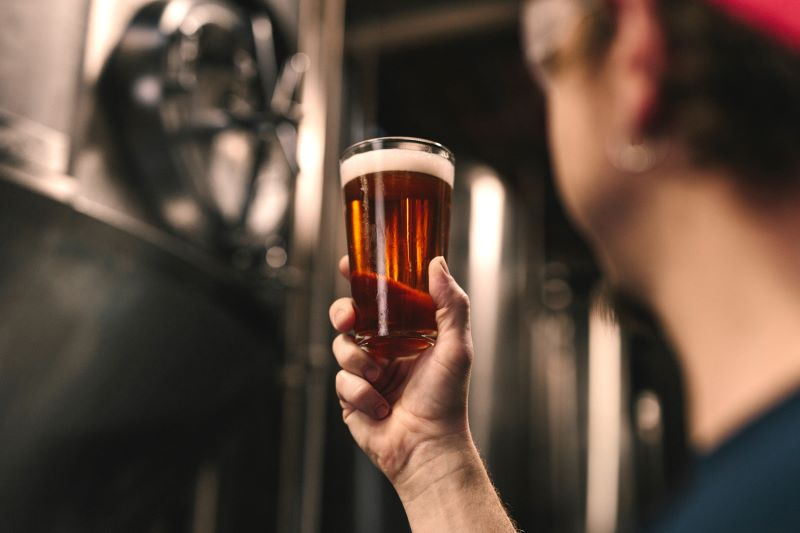 Man holding up a pint of beer from a Cotswold brewery