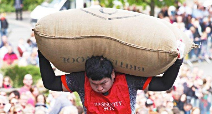 A competitor carrying the 70lb woolsack
